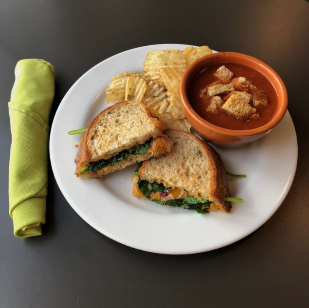 Picture of a place setting with a grilled cheese sandwich, a cup of tomato soup with croutons, a side of potato chips, and a green roll of silverwear.